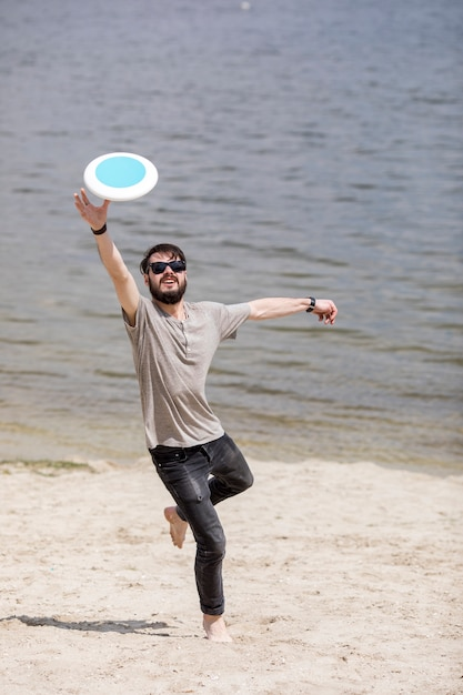 Erwachsener mann, der frisbee auf strand laufen lässt und fängt Kostenlose Fotos
