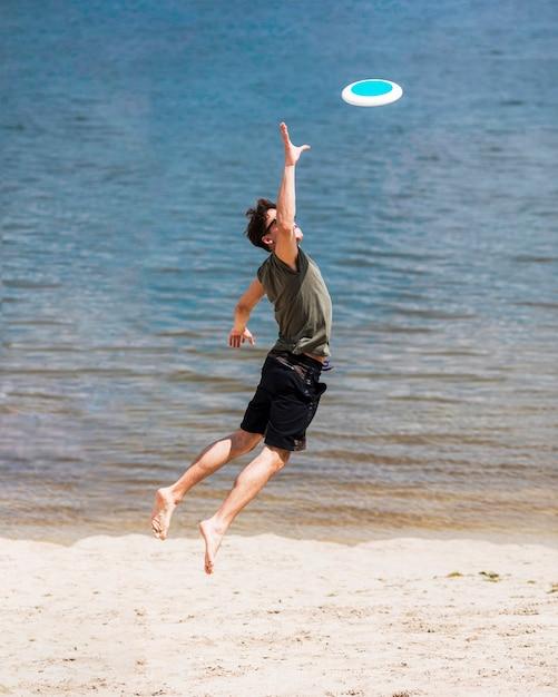 Erwachsener mann, der für anziehende frisbee-diskette springt Kostenlose Fotos