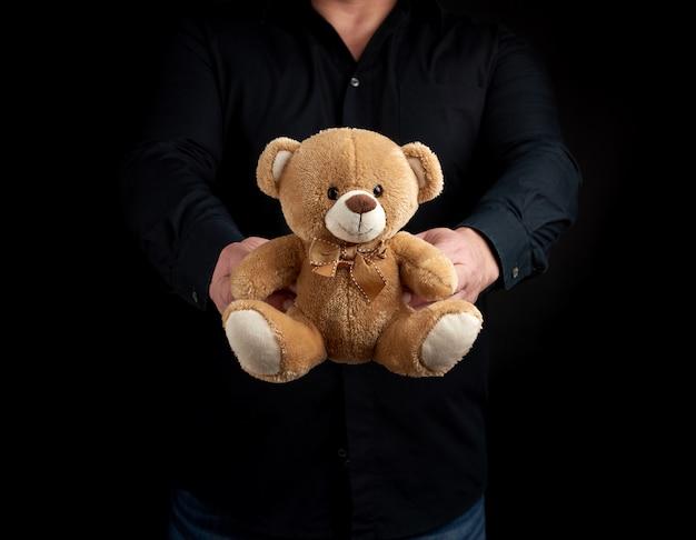 Erwachsener mann in einem schwarzen hemd hält einen braunen teddybären Premium Fotos