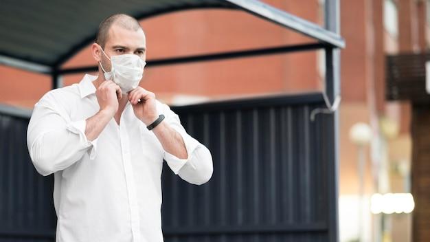 Erwachsener mann mit chirurgischer maske, die auf den bus wartet Kostenlose Fotos