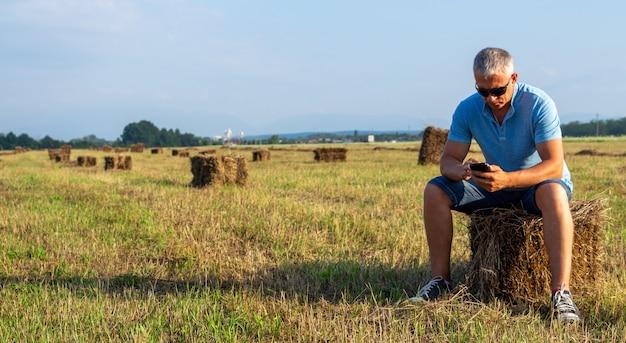 Erwachsener mann mit einem telefon sitzt auf einem heuhaufen. Premium Fotos