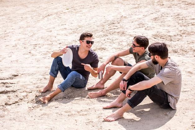 Erwachsener mann mit frisbee-freunden am strand sitzen Kostenlose Fotos