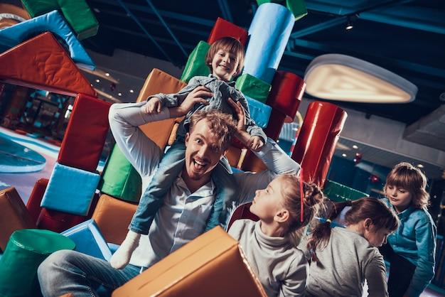 Erwachsener mann und nette kinder auf innenspielplatz Premium Fotos