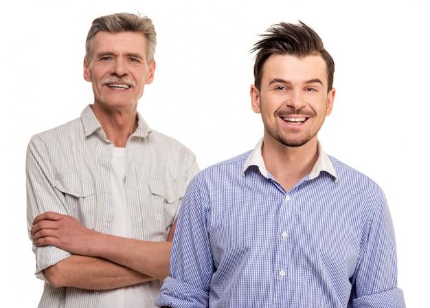 Erwachsener sohn mit dem älteren vater, der auf weiß lächelt Premium Fotos