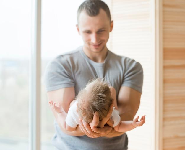 Erwachsener vati, der baby auf händen hält Kostenlose Fotos