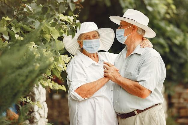 Erwachsenes paar in einem sommergarten. coromavirus-thema. menschen in einer medizinischen maske. hübscher senior in einem weißen hemd. Kostenlose Fotos