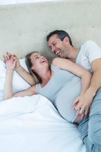 Erwartung der paare, die auf bett liegen und in ihrem schlafzimmer plaudern Premium Fotos