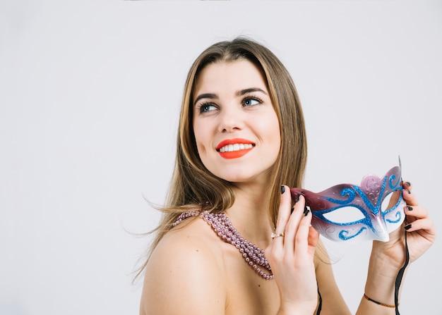 Erwogene lächelnde frau mit der perlenhalskette, die maskeradekarnevalsmaske hält Kostenlose Fotos