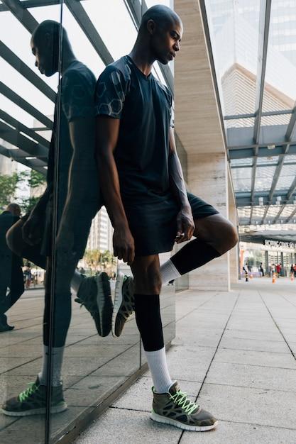 Erwogener afrikanischer junger männlicher athlet, der auf reflektierendem spiegel an draußen sich lehnt Kostenlose Fotos