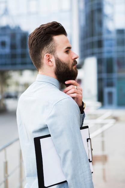 Erwogener junger geschäftsmann mit dem klemmbrett, das seinen bart berührt Kostenlose Fotos