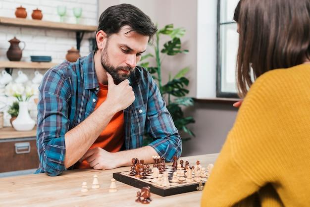 Erwogener junger mann, der zu hause das schachspiel mit ihrer frau spielt Kostenlose Fotos