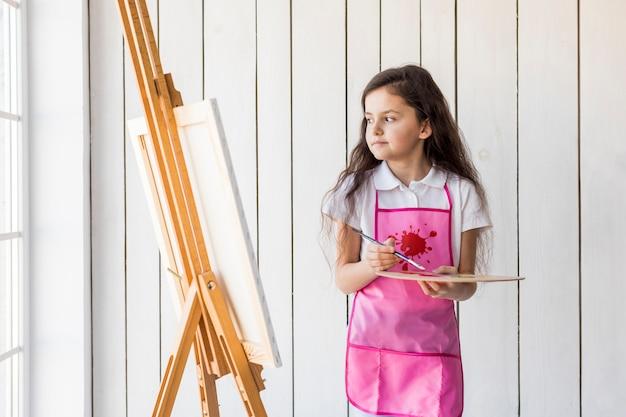 Erwogenes kleines mädchen mit dem rosa schutzblech, das malerpinsel und palette hält Kostenlose Fotos