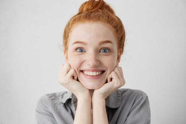 Erzähl mir mehr. nahaufnahme schuss der neugierigen 20-jährigen rothaarigen kaukasischen frau, die gesicht auf ihren händen kissen und mit vorfreude und aufregung schauen, während geschichte oder klatsch hören Kostenlose Fotos