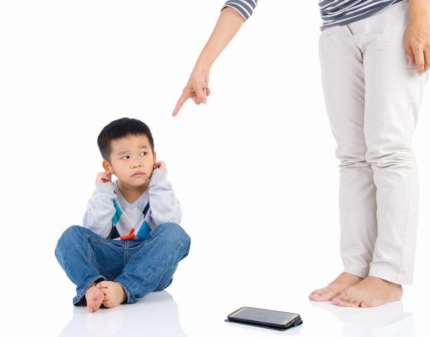 Erziehung des kindes. mutter schimpft mit ihrem kinderjungen auf smartphone. Premium Fotos
