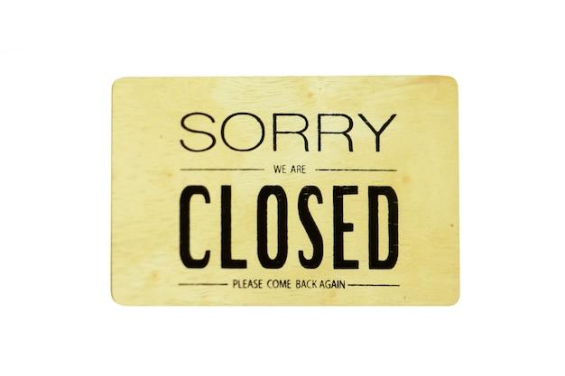 Es tut uns leid, dass wir auf dem hölzernen hängenden zeichen geschlossen sind, das auf weiß lokalisiert wird. Premium Fotos