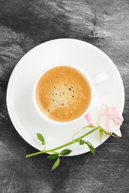 Espressokaffee in einer weißen schale, in einer rosa rose und in schokoladen auf einem dunklen hintergrund. ansicht von oben. essen hintergrund. Premium Fotos