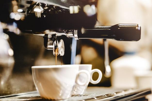 Espressomaschine, die einen kaffee braut. kaffee, der in gläser in der kaffeestube, espresso gießt aus kaffeemaschine gießt Premium Fotos