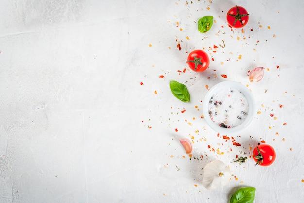 Essen hintergrund. zutaten, gemüse und gewürze zum kochen mittagessen. frische basilikumblätter, tomaten, knoblauch, zwiebeln, salz, pfeffer. auf einem weißen steintisch. kopieren sie die draufsicht des raumes Premium Fotos