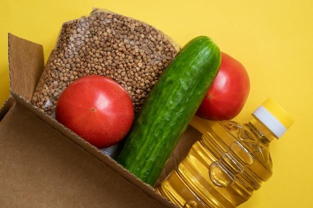 Essen in einem karton auf gelbem grund Kostenlose Fotos