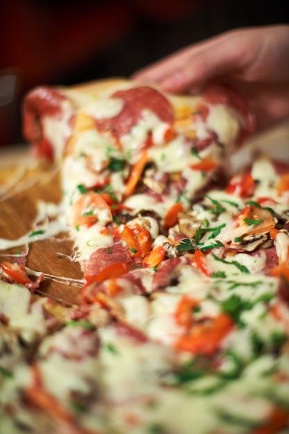 Essenszeit in der pizzeria, mann nimmt ein stück pizza mit sehr geringer schärfentiefe. rahmen. übergeben sie geschnittenes stück pizza und nehmen sie es, abschluss, makroschuß auf. pizza und stück pizza in der hand Premium Fotos