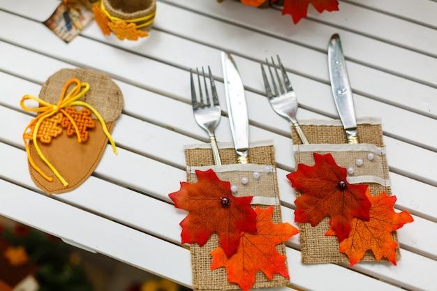 Essgeschirrgabeln und -messer, die einen holztisch verziert mit herbstlaub dienen Premium Fotos