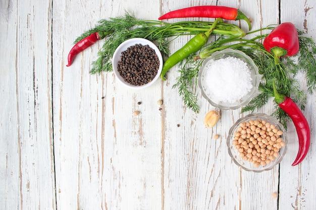 Essiggurken auf weißem holztisch mit den grünen und roten und paprikapfeffern, fenchel, salz, schwarzen pfefferkörnern, knoblauch, erbse, abschluss oben, gesundes konzept, draufsicht, ebenenlage Kostenlose Fotos