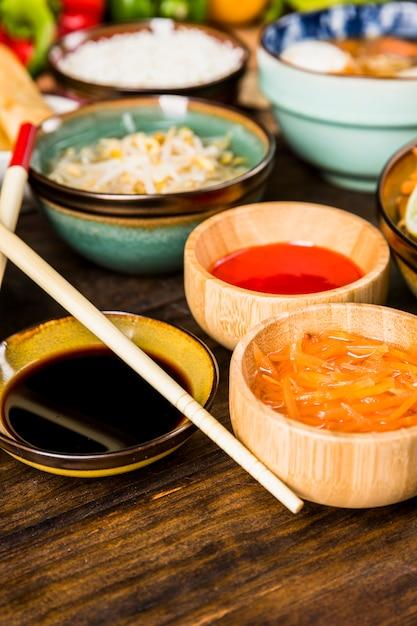 Essstäbchen in nahaufnahme mit soja; rote chilisaucen und geriebene karotten in holzschale auf dem schreibtisch Kostenlose Fotos