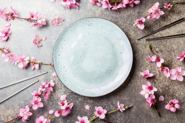 Essstäbchen und kirschblüte verzweigt sich auf grauen stein Premium Fotos