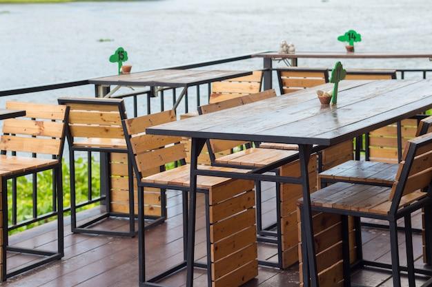 Esstisch im gemütlichen straßencafé. esstisch neben dem flusscafé. Premium Fotos