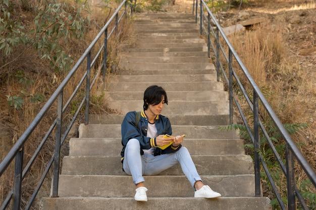 Ethnischer jugendlicher, der mit buch auf treppen sitzt Kostenlose Fotos