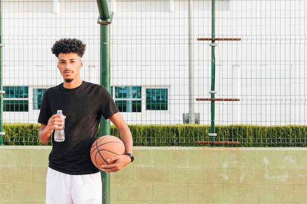 Ethnischer junger mann, der basketball am gericht hält Kostenlose Fotos