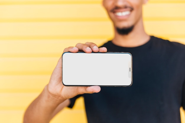 Ethnischer mann der ernte, der smartphone zeigt Kostenlose Fotos