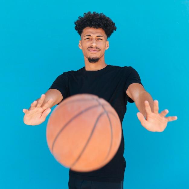 Ethnischer werfender basketball des jungen mannes an der kamera Kostenlose Fotos