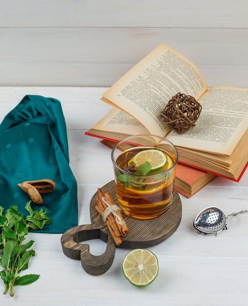 Etwas kräutertee und zimt mit büchern, zitrone, gewürzen und grünem schal auf einem holzbrett Kostenlose Fotos