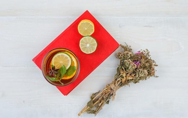 Etwas kräutertee und zitrusfrüchte mit einem blumenstrauß auf einem roten tischset Kostenlose Fotos