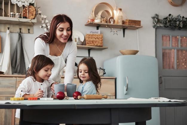Etwas leckeres geben. junge schönheit geben den kindern getränke, während sie nahe der tabelle mit spielwaren sitzen Premium Fotos
