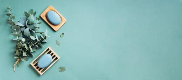 Eukalyptusätherisches öl und -seife auf grünem hintergrund. null abfall, natürliche organische badezimmerwerkzeuge. Premium Fotos