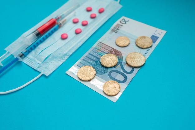 Euro-banknoten und -münzen. medizinische maske, impfstoffspritze und rosa pillen. wirtschaftskrise. gesundheitsausgaben. ausbruch des coronavirus. Premium Fotos