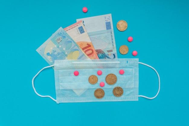 Euro-banknoten und -münzen. medizinische maske und rosa pillen. wirtschaftskrise. gesundheitsausgaben. ausbruch des coronavirus. Premium Fotos