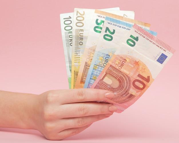 Euro-banknotengeld in den weiblichen händen auf rosa hintergrund. geschäftskonzept und instagram Premium Fotos
