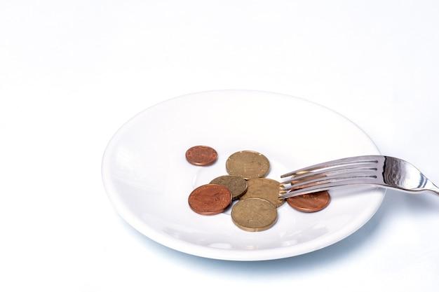 Euro-cent-münzen auf einem weißen teller mit einer gabel auf einem weißen Premium Fotos