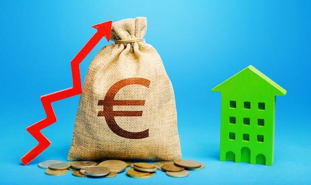 Euro-geldsack mit rotem pfeil und wohngebäude. kapitalrendite Premium Fotos