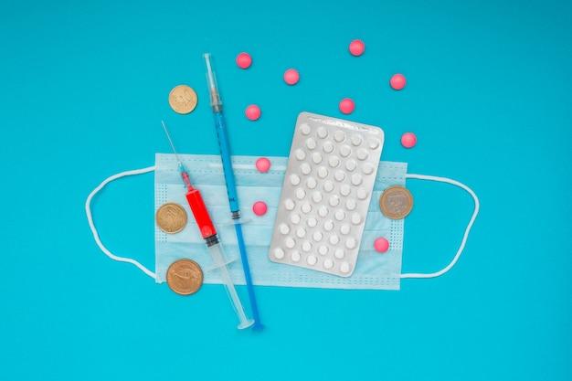 Euro-münzen. medizinische maske, impfstoffspritze und rosa pillen, pillenblase. wirtschaftskrise. gesundheitsausgaben. ausbruch des coronavirus. Premium Fotos
