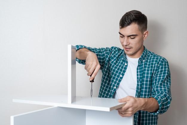 Europäer mit einem schraubenzieher in der hand sammelt einen weißen tisch Premium Fotos