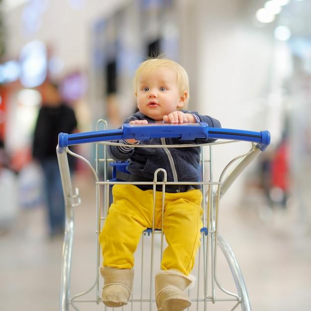 Europäischer kleinkindjunge, der im einkaufswagen sitzt Premium Fotos