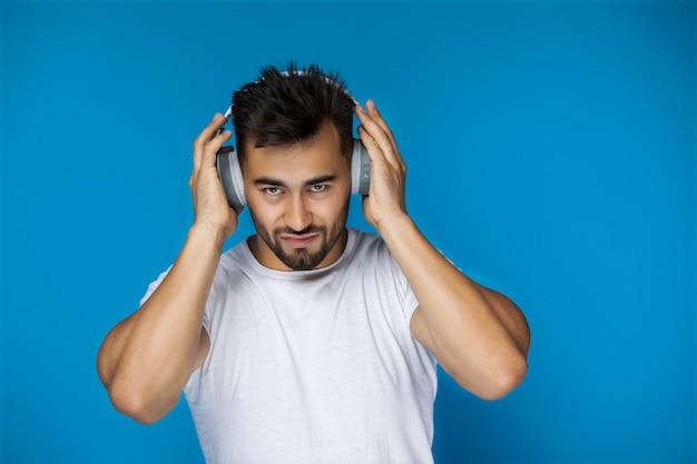 Europäischer mann im weißen t-shirt hört musik durch kopfhörer Kostenlose Fotos