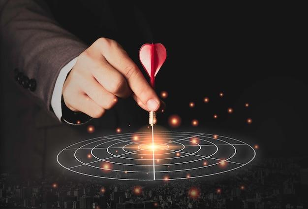 Executive marketing hand hält roten pfeil in die mitte der zieltafel gelegt. geschäftsinvestitionsziel und zielkonzept. Premium Fotos