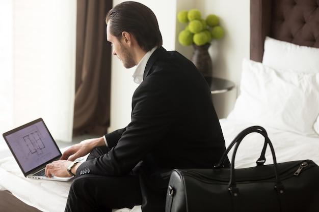 Exekutive überprüft standplan auf laptop im hotel Kostenlose Fotos