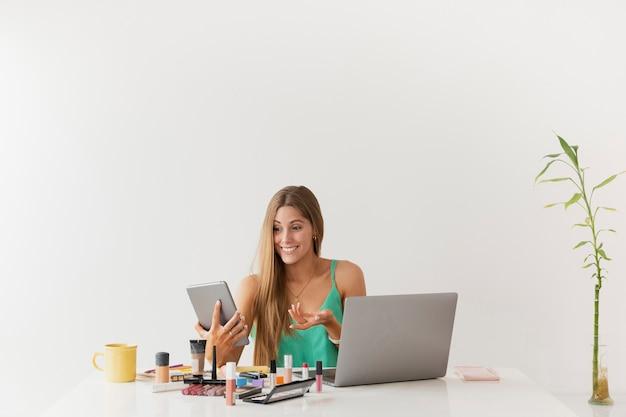 Exemplarplatzfrau am schreibtisch mit schönheitsprodukten Kostenlose Fotos