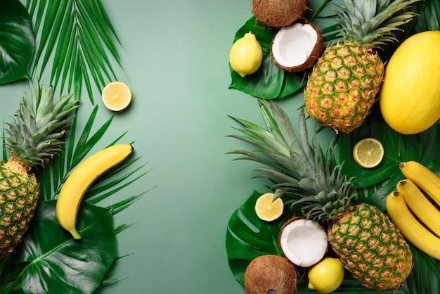 Exotische ananas-, kokosnuss-, bananen-, melonen-, zitronen-, tropische palmen- und monsterblätter auf grün. Premium Fotos